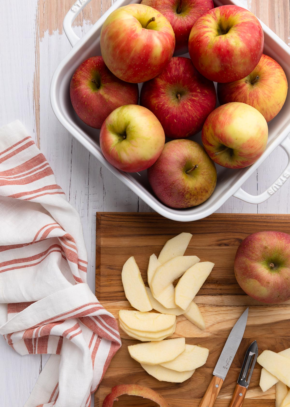 overhead photo of honeycrisp apples in a white baking dish, with sliced apples on a wood cutting board