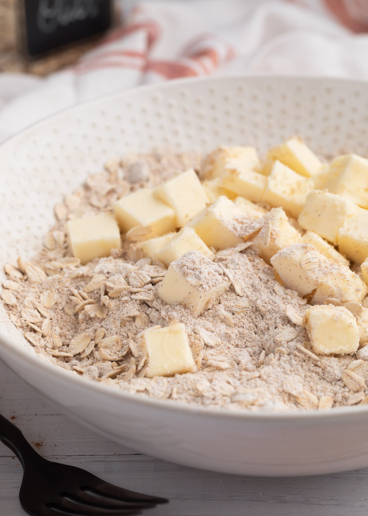 cubes of butter in a bowl of brown sugar, oats, and flour