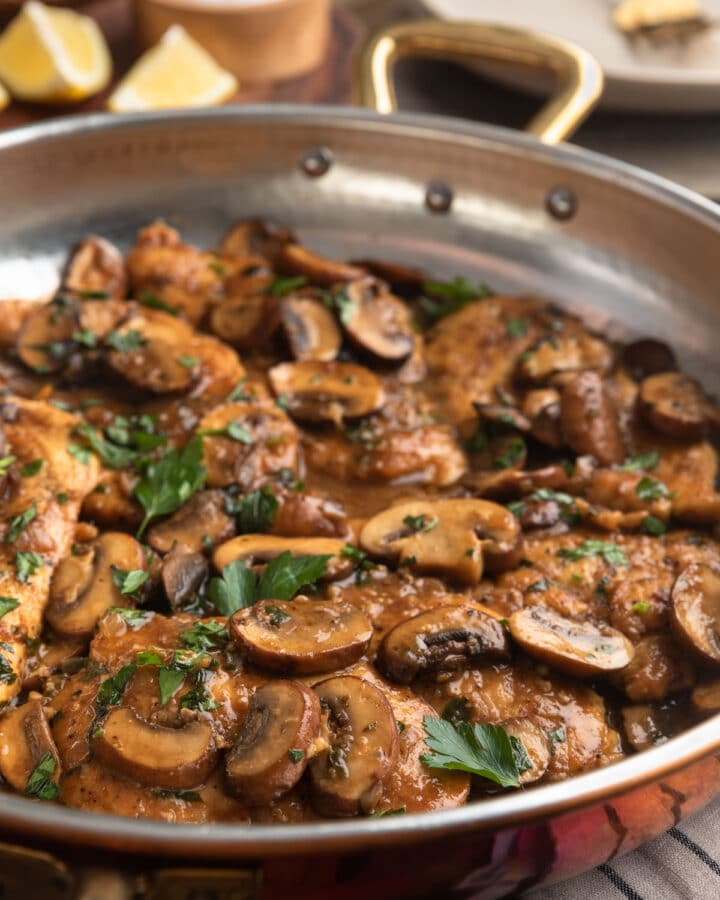 side view of chicken marsala in a copper frying pan