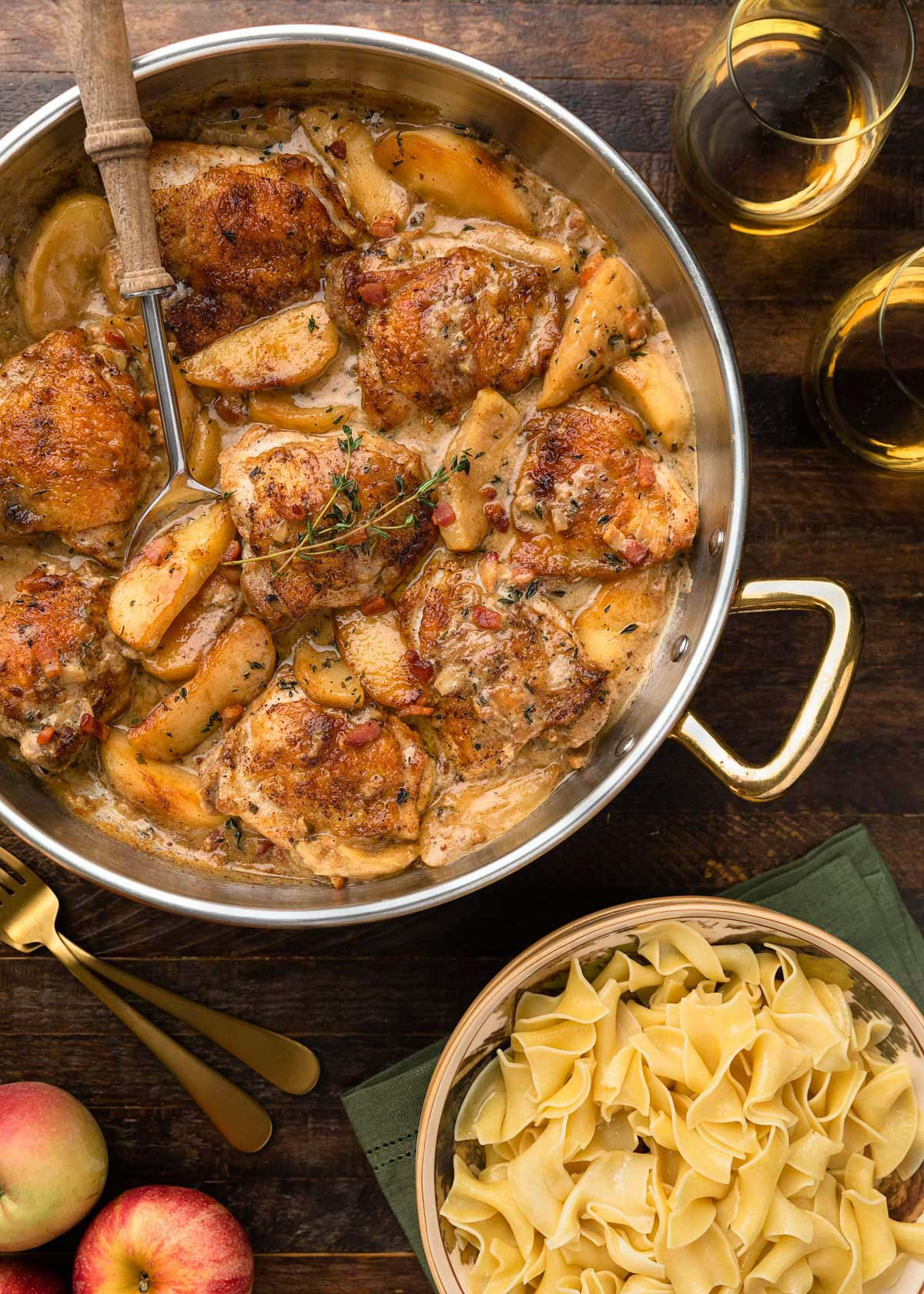 chicken thighs and apples in a copper frying pan with hard cider sauce next to a bowl of egg noodles