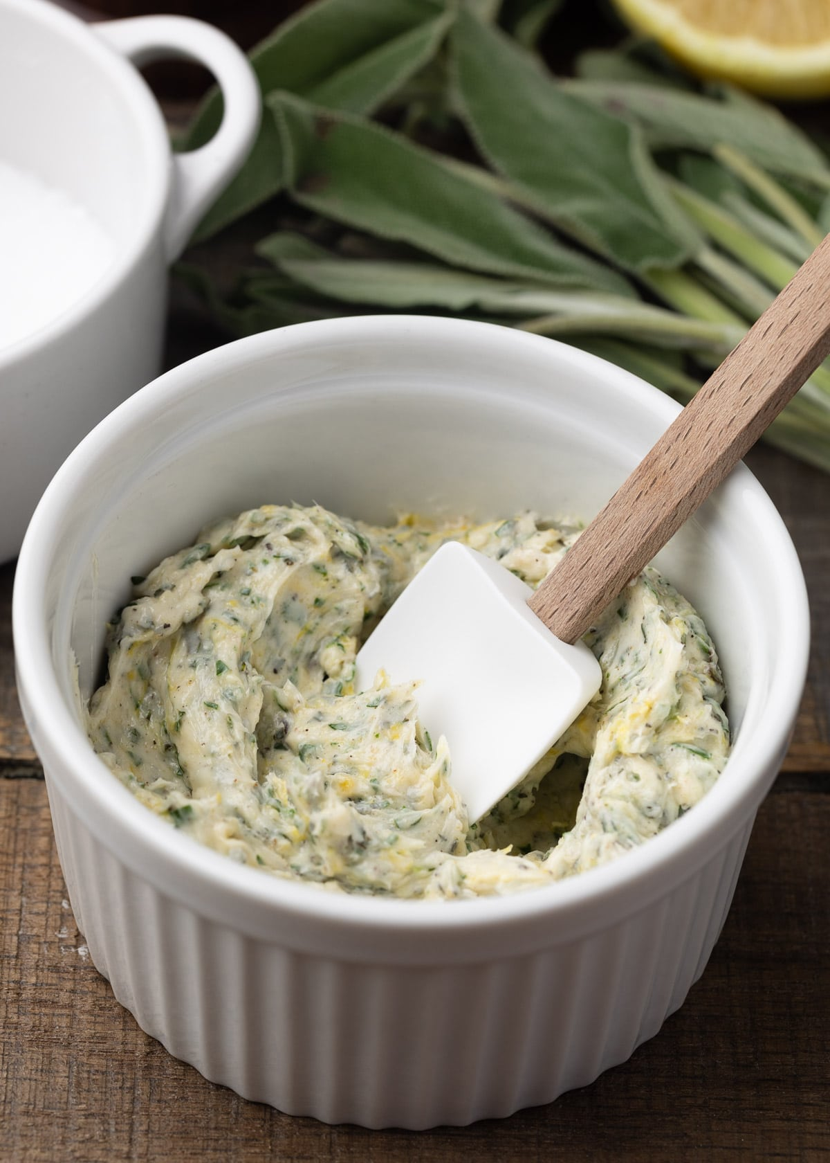 herb compound butter in a white ramekin with a small white spatula