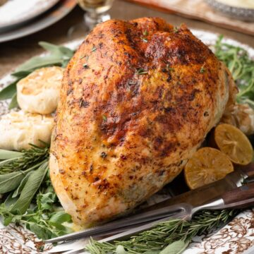 herb roasted turkey breast on a platter with fresh herbs and roasted garlic