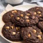 chocolate chip peanut butter cookies on a parchment lined dish with a glass of milk