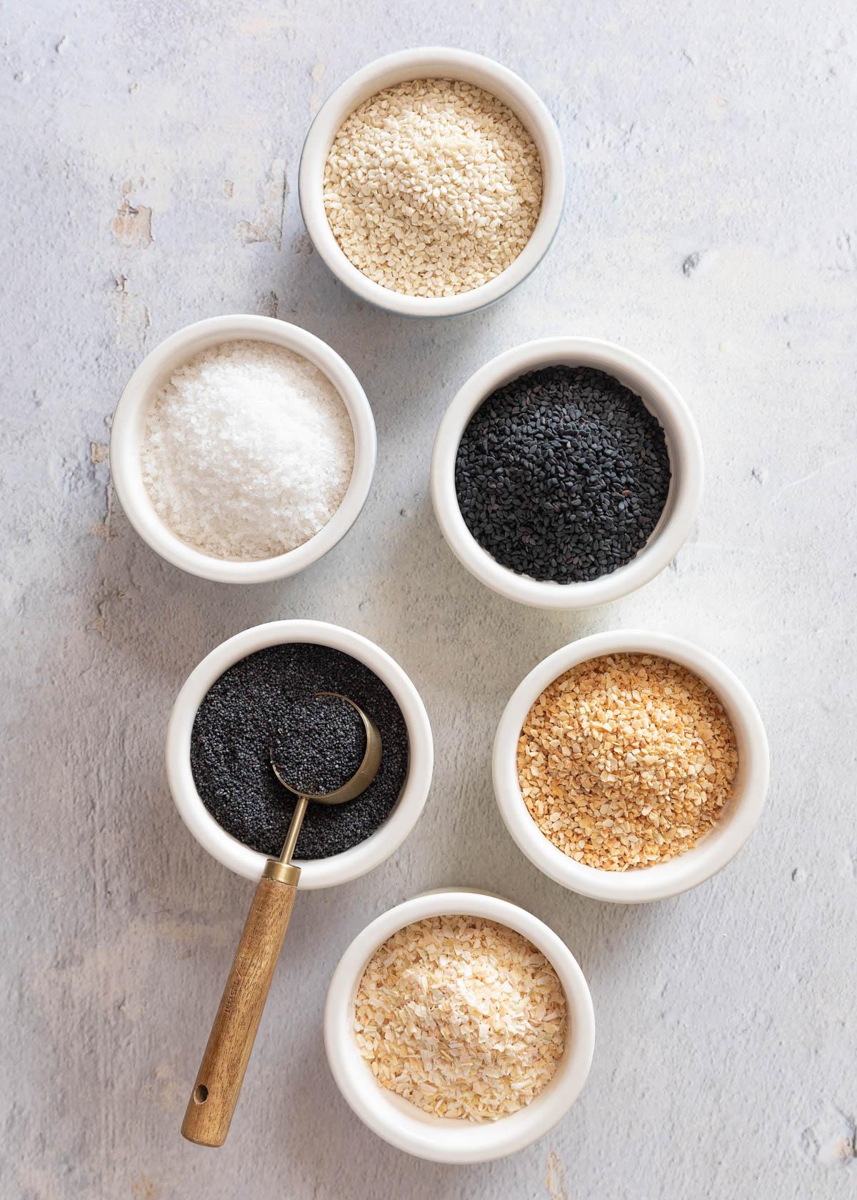 ingredients to make homemade everything bagel seasoning in ceramic bowls