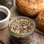everything bagel seasoning in a glass jar, surrounded by everything bagels on a wood board