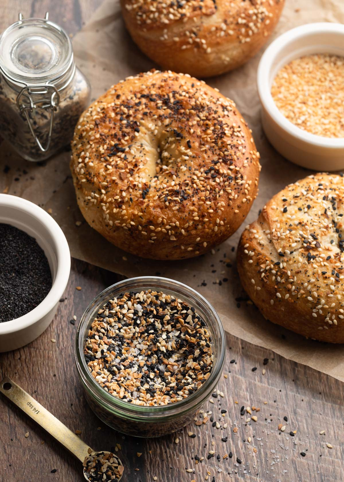 everything bagel seasoning in a jar with bowls of poppy seeds, minced dried garlic, and bagels