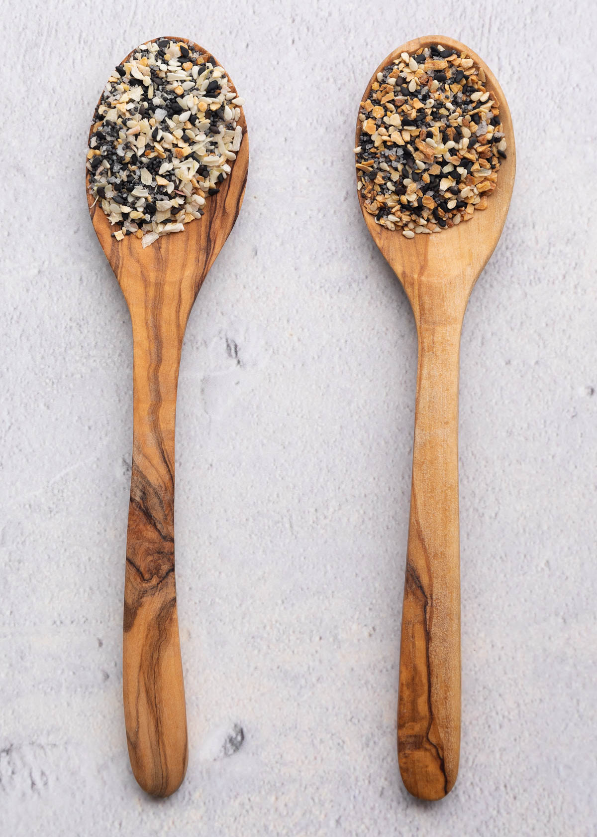 two olive wood spoons with untoasted and toasted everything seasoning