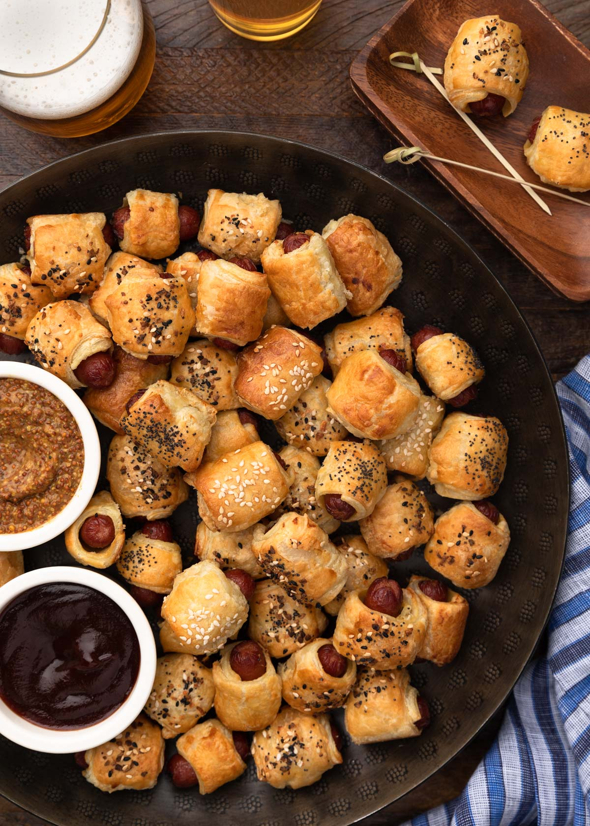 overhead of pigs in a blanket on a round serving platter with dipping sauces