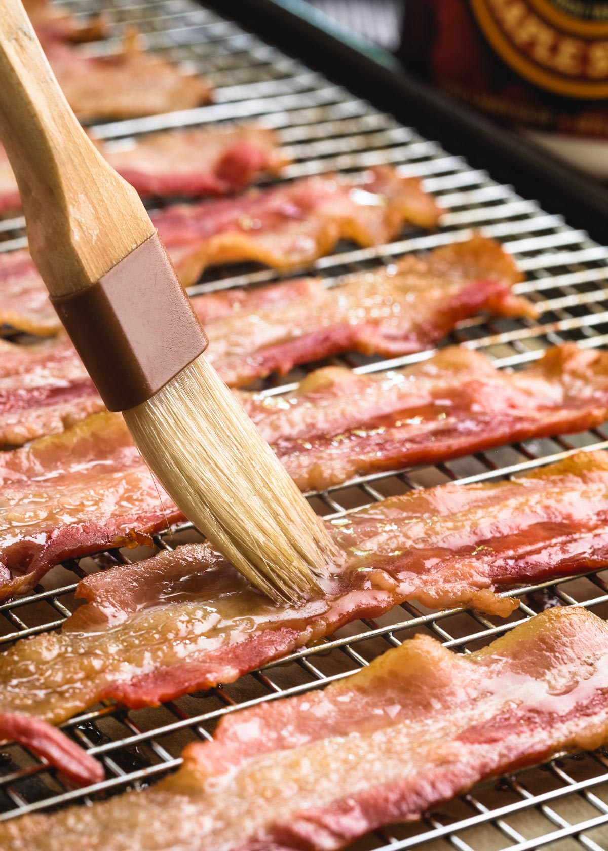 maple syrup being brushed onto partially-baked bacon strips on a wire rack