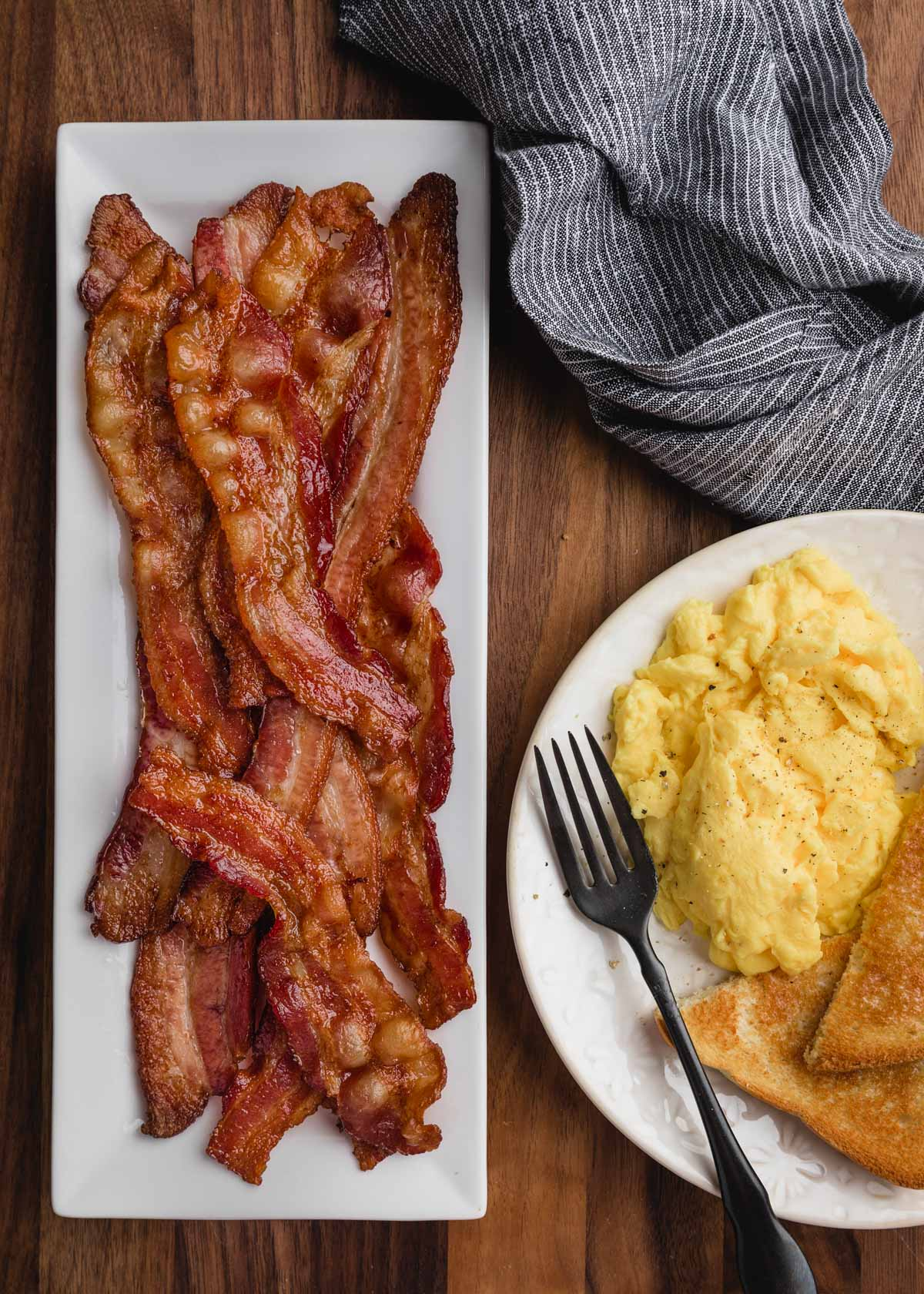 overhead of bacon on a white rectangular platter with a breakfast plate of eggs on the side