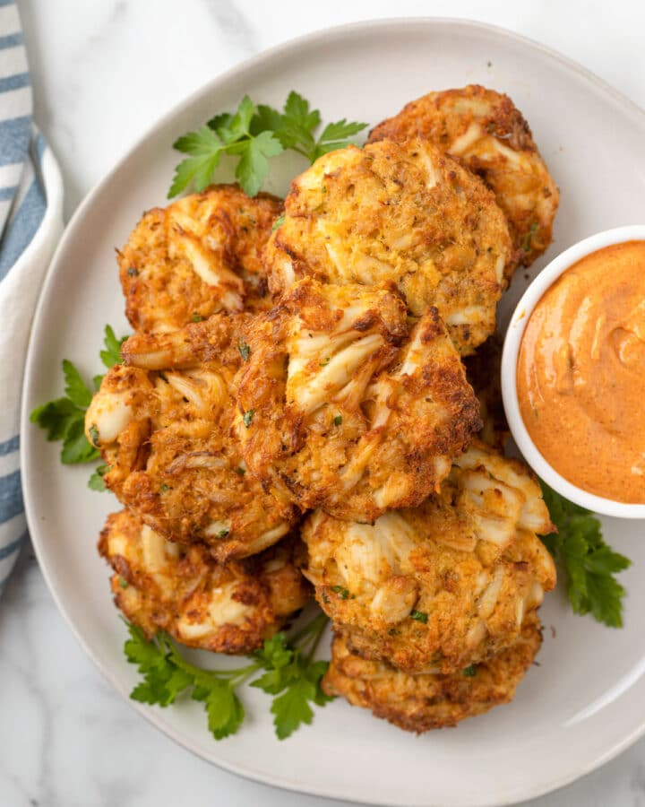 overhead photo of air fried crab cakes on a white plate with a bowl of remoulade