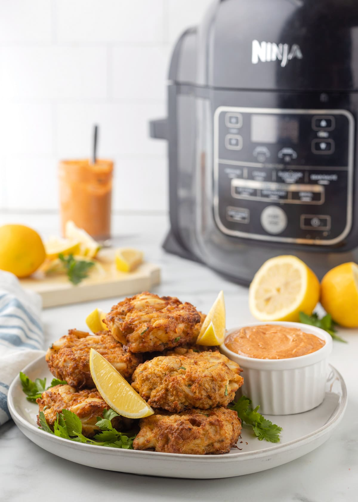 air fryer crab cakes on a white plate with lemon wedges and remoulade in front of a ninja foodi air fryer