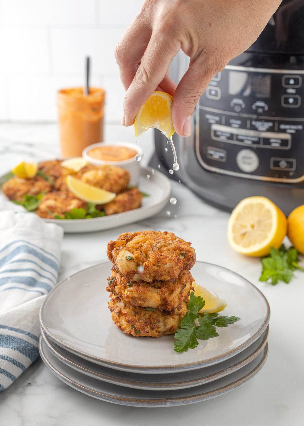 squeezing lemon over three crab cakes stacked on gray plates