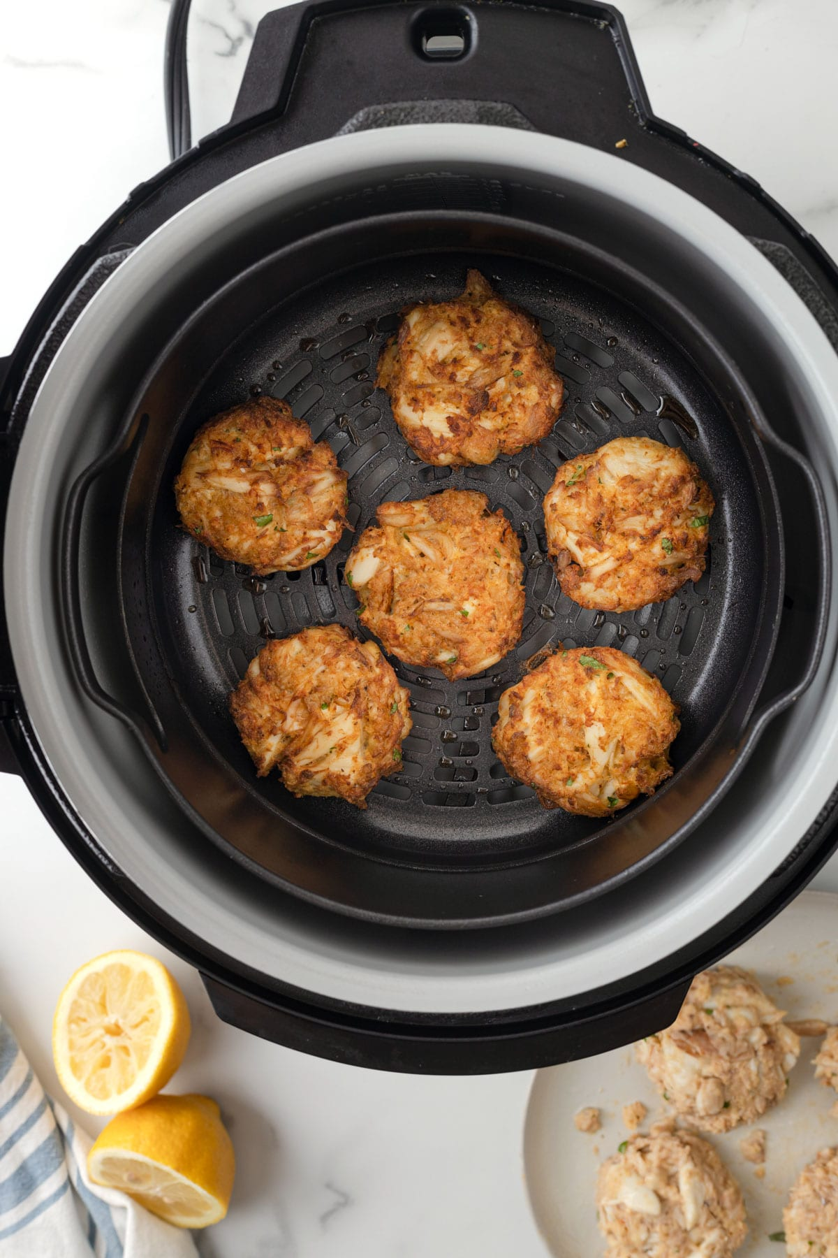 overhead of cooked crab cakes in an air fryer basket