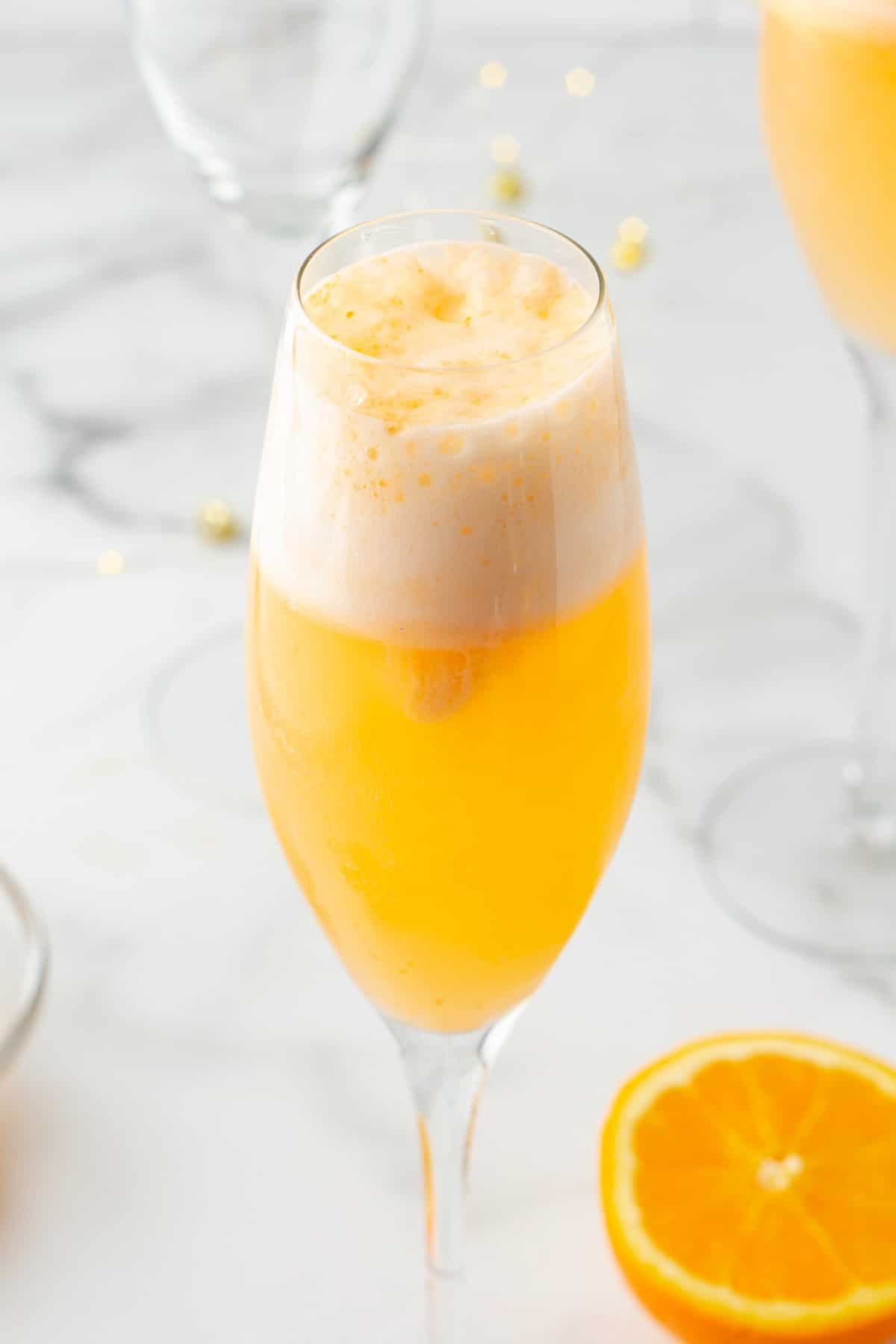 side view of an orange sherbet mimosa mocktail in a champagne flute