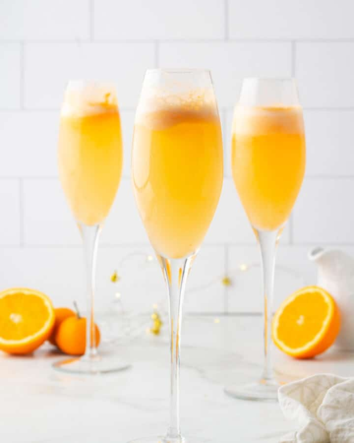 three orange sherbet mimosa mocktails in champagne flutes