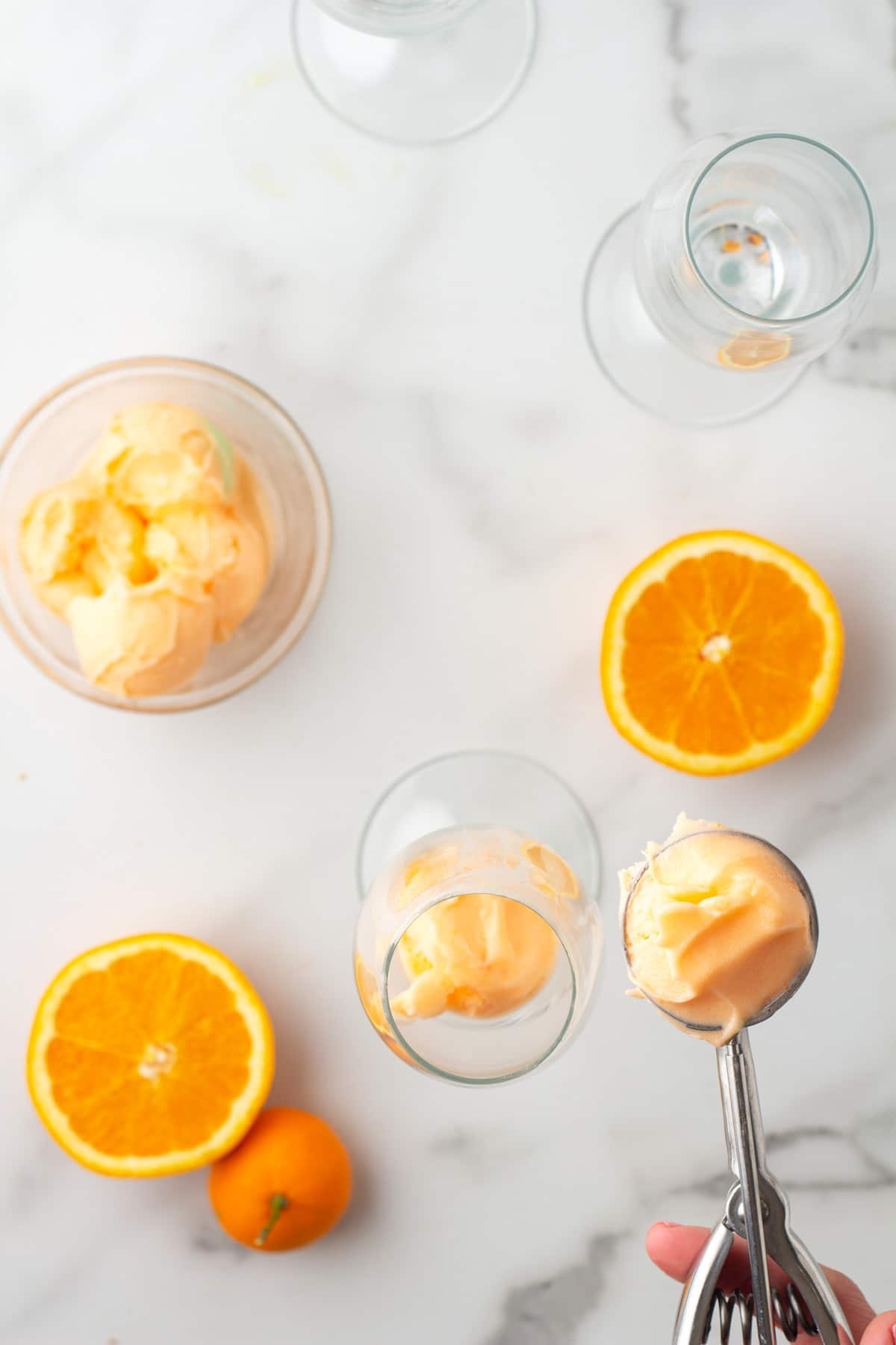 overhead view of scooping orange sherbet into a champagne glass with an ice cream scoop