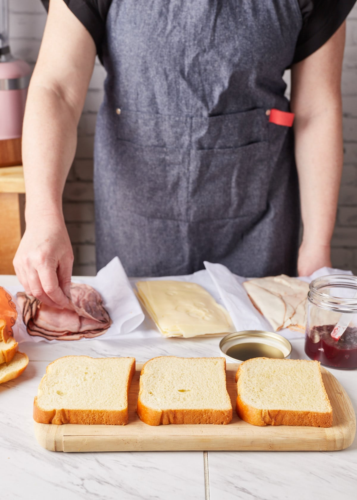 three slices of bread on a wood cutting board, in front of piles of deli meat and cheese, and a woman in an apron in the background picking up a slice of ham