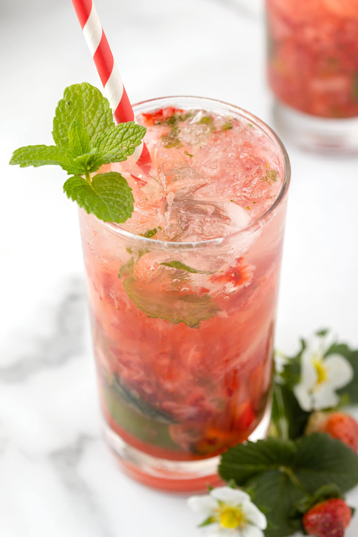 closeup of a strawberry mojito in a highball glass with a sprig of mint