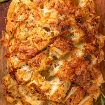 overhead photo of cheesy garlic pull apart bread on a wooden cutting board