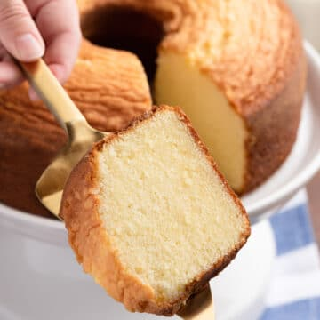 slice of vanilla pound cake on a gold cake server in front of a full pound cake on a white cake stand