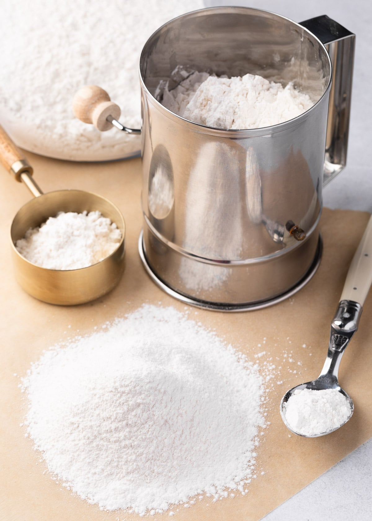 cake flour sifted onto a piece of parchment paper next to a stainless steel sifter